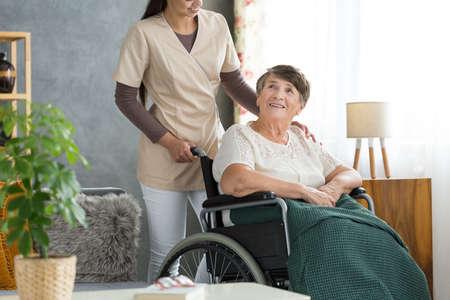 Foto de Nurse supporting happy elderly woman in wheelchair with green blanket on legs in nursing home - Imagen libre de derechos