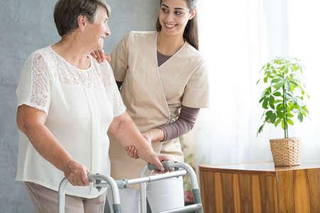 Foto de Smiling nurse in uniform helping old lady with walker during visit at home - Imagen libre de derechos