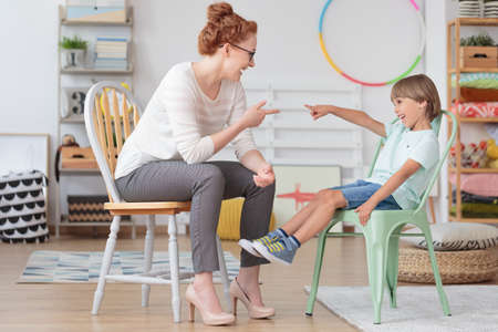 Foto de Professional female tutor having fun playing and working with little boy during private lesson at home - Imagen libre de derechos