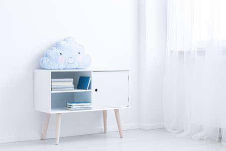 Foto de White scandi cupboard with books and pastel blue pillow in white room - Imagen libre de derechos