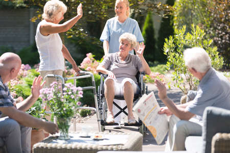 Photo pour Elderly people welcoming a woman in a wheelchair during meeting in garden on sunny day - image libre de droit
