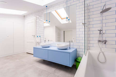 Photo for Stainless steel shower set and bathtub next to blue washbasin cabinet in bright bathroom in attic - Royalty Free Image