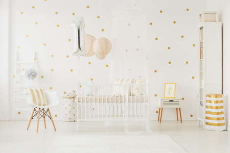 Foto für Silver balloon with helium for baby's birthday pinned to white crib in dotted wall room - Lizenzfreies Bild