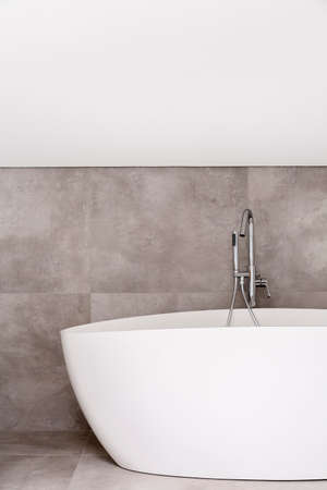 Photo for Oval bathtub with stainless steel faucet in empty bathroom with grey glaze - Royalty Free Image