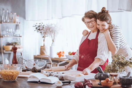 Photo pour Granddaughter hugging grandmother while making cake together in the kitchen - image libre de droit