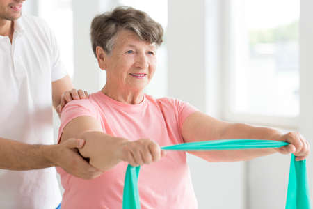 Photo pour Senior woman stretching with green resistance band during individual rehabilitation - image libre de droit