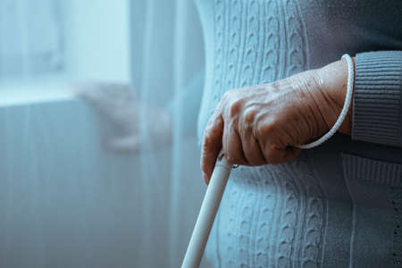 Photo pour Close-up of blind person holding white cane while walking in room - image libre de droit