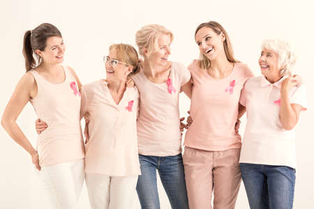 Photo for Smiling women of five generations with pink ribbons embracing each other, breast cancer concept  - Royalty Free Image