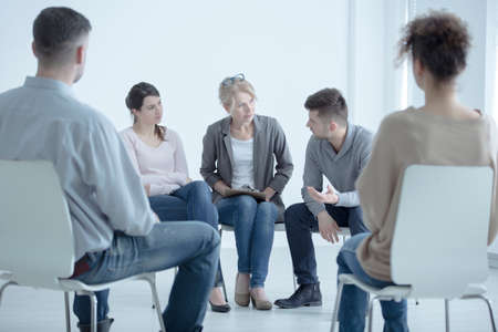 Foto de Man talking to a psychotherapist about family problems during meeting with support group - Imagen libre de derechos