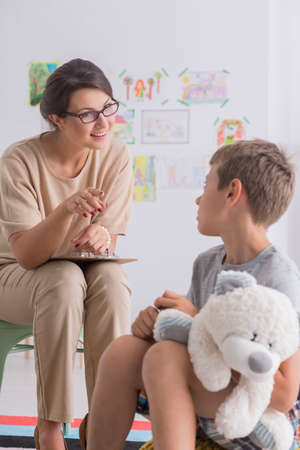 Foto de Friendly educational psychologist and little boy with autism successful therapy session - Imagen libre de derechos