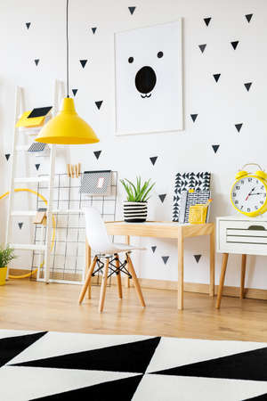 Photo for Yellow clock on white cabinet next to wooden desk and white chair in contrast color kindergarten - Royalty Free Image
