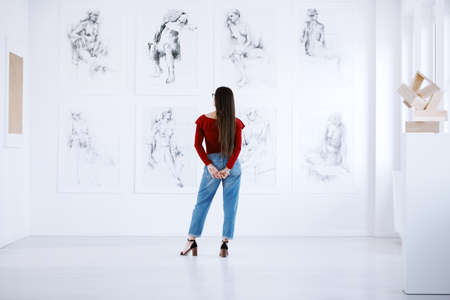 Photo pour Fashionable woman looking at a display of paintings of female nudity in an art museum - image libre de droit