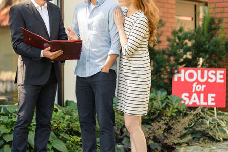 Photo for Close-up of young couple negotiating conditions of contract with house seller - Royalty Free Image