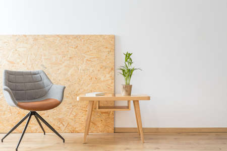 Foto de Designer chair next to a wooden table with plant and book against the wall with copy space - Imagen libre de derechos