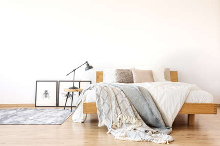 Photo for Bedsheets on wooden king-size bed against white wall in spacious bedroom with lamp on a stool - Royalty Free Image