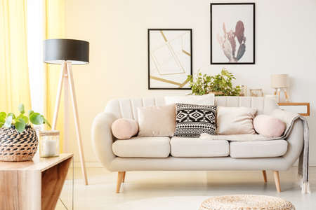 Foto de Patterned pillow on a beige couch next to lamp and plant on a cabinet in simple living room with posters on the wall - Imagen libre de derechos
