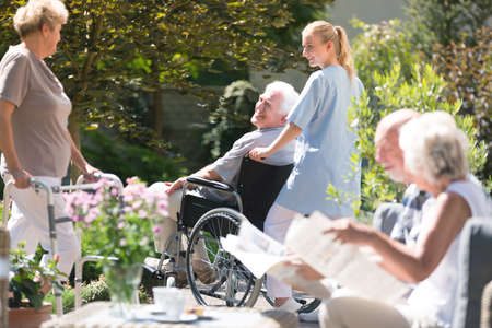 Foto de Nurse supporting senior man in a wheelchair during meeting with friends in the garden on sunny day - Imagen libre de derechos