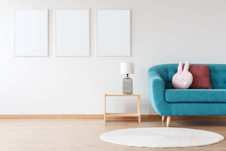 Photo for Mockup of white posters and lamp on wooden stool in child's room with blue sofa and white carpet - Royalty Free Image