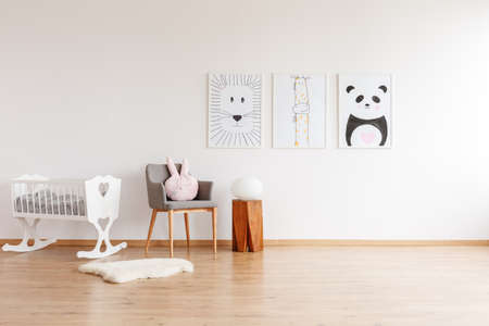 Foto de Drawings on white wall above grey chair with pillow and wooden stool in baby's room with white crib and rug - Imagen libre de derechos