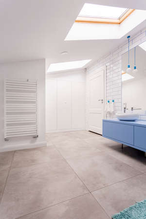 Photo for Spacious rest room with white heater on wall and light bulbs above blue washbasin cabinet with mirror - Royalty Free Image