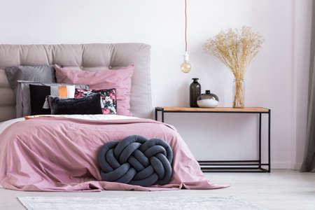 Foto de Wooden bedside table and blue handmade pillow next to bed with pink overlay in stylish apartment with simple bedroom decor - Imagen libre de derechos