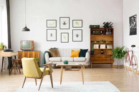 Foto de Yellow chair at wooden table on white carpet in retro living room with television on cabinet next to sofa - Imagen libre de derechos