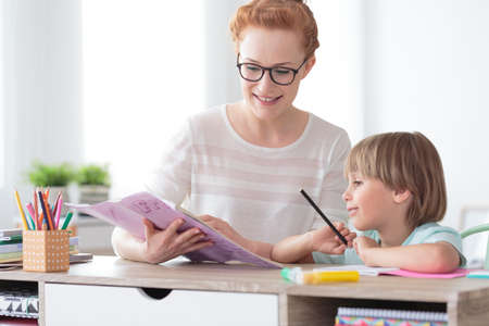 Photo for Young female tutor helping little elementary school boy with homework during individual lesson at home - Royalty Free Image