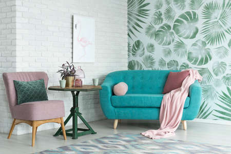 Photo pour Green table with a plant between pink chair and blue sofa in floral living room with wallpaper and poster - image libre de droit