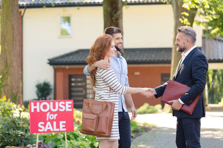 Photo for Seller congratulating a young couple buying house in suburbs - Royalty Free Image