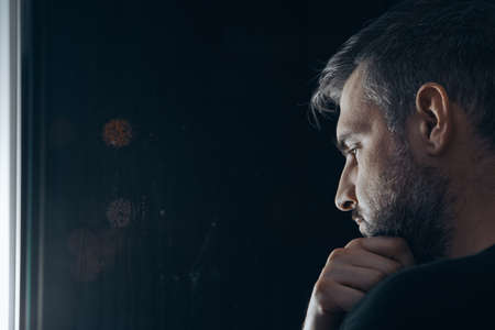 Photo for Man with beard holding his chin, standing beside a window at night - Royalty Free Image