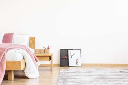 Foto de DiY posters next to a wooden nightstand and bed with pink blanket in bedroom with copy space on empty wall - Imagen libre de derechos