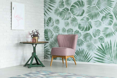 Photo pour Pink chair at green table with a plant in gold pot in room with poster on white brick wall and floral wallpaper - image libre de droit