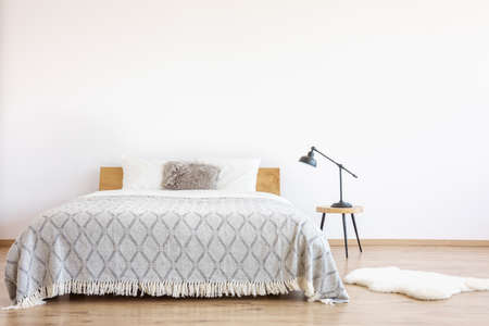 Photo for Patterned blanket on king-size bed with fur pillow in a simple bedroom with rug and lamp on stool - Royalty Free Image
