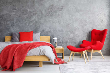Foto de Red armchair and stool next to wooden bed against concrete wall with copy space in bedroom - Imagen libre de derechos