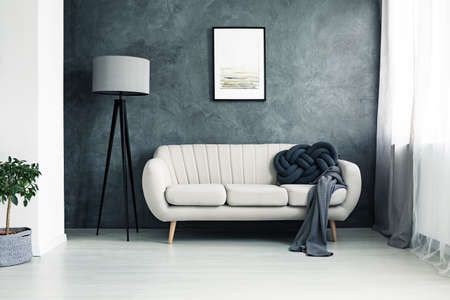 Foto de Bright couch with handmade knot cushion and grey blanket standing in a living room with lamp and poster hanging on textured wall - Imagen libre de derechos
