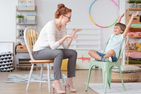Foto de Child psychologist and young kid with ADHD during therapy session in primary school interior - Imagen libre de derechos