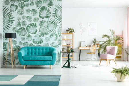 Photo pour Spacious room with lamp next to blue couch against green wallpaper and pink chair near workspace - image libre de droit