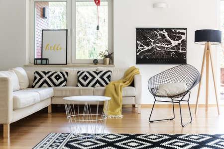Photo pour Bright living room interior design with white table, corner sofa and black poster - image libre de droit