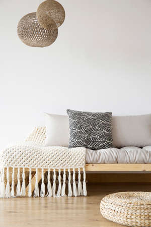 Foto de Patterned blanket on wooden bed, pouf and lamps in bright bedroom with copy space on white wall - Imagen libre de derechos