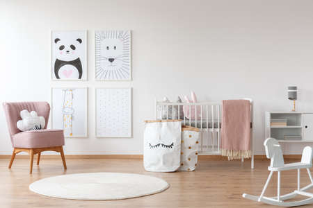 Foto de White rocking horse and carpet in child's room with pink armchair, paper bags, drawings and bed - Imagen libre de derechos