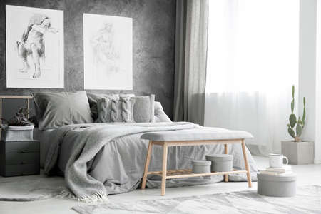 Foto de Wooden bench and cactus in bright grey bedroom with bed against textured wall with drawings - Imagen libre de derechos
