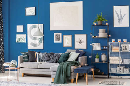 Photo pour Patterned blanket on corner sofa in living room with stool, tables and posters on blue wall - image libre de droit