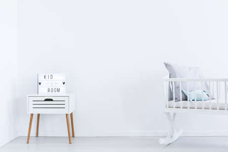 Foto de Decoration on white cabinet next to white cradle in empty interior with white wall - Imagen libre de derechos