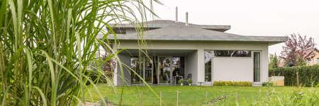 Foto de View of the grey family house surrounded by well-kept lawn - Imagen libre de derechos