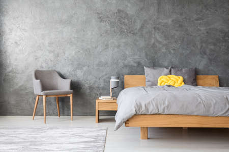 Foto de Grey interior of a spacious monochromatic bedroom with a yellow pillow lying on a king-size bed - Imagen libre de derechos