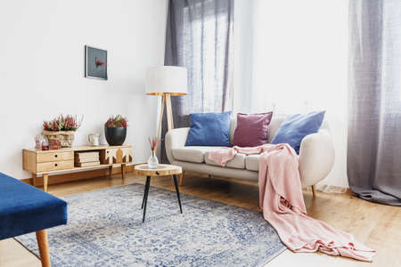 Foto de Wooden stool with glass vase on patterned carpet next to sofa with pink blanket in cozy living room interior with rustic cupboard - Imagen libre de derechos