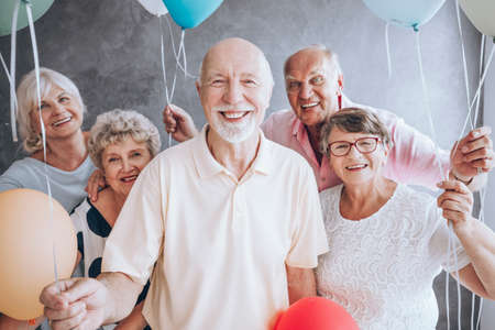Foto de Smiling elderly man and his friends with balloons enjoying his birthday party - Imagen libre de derechos