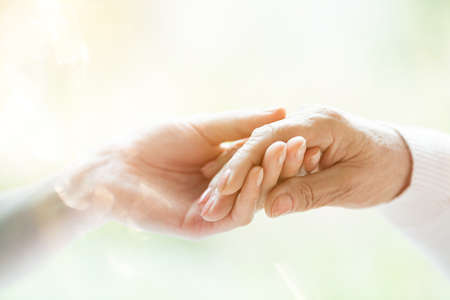 Photo pour Close-up of young person's hand holding elderly person's hand as sign of caring for seniors - image libre de droit