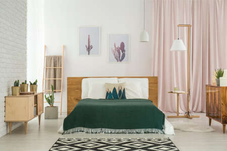 Photo pour Dark blanket on king-size bed and geometric carpet in rustic bedroom with wooden furniture - image libre de droit