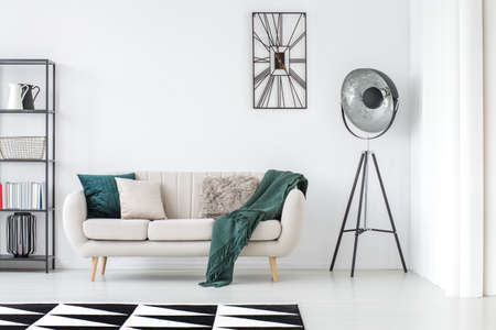 Photo pour Green blanket on beige settee in bright living room with lamp and clock on white wall with copy space - image libre de droit